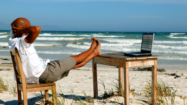 Man with laptop at beach